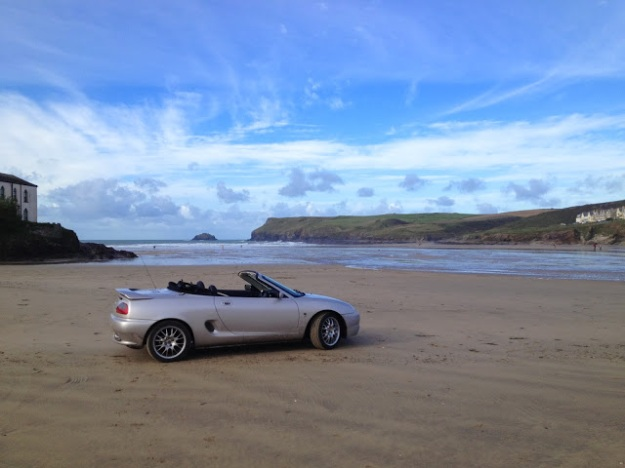 The MGF Freestyle on Polzeath Beach, complete with surfboard on the passenger seat